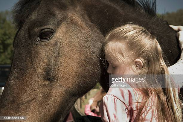 girl (5-7) embracing horse - hairy little girls stock photos and pictures