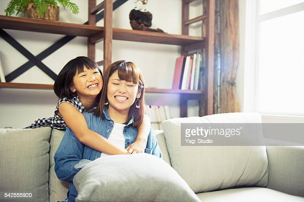 Girl embracing mother at home.