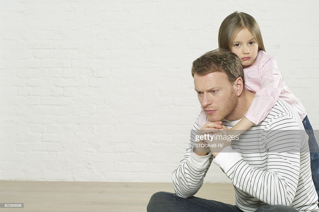 Girl embracing reflective father from behind : Stock Photo