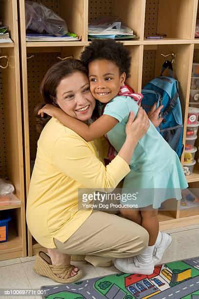 Girl (4-5) embracing teacher, smiling