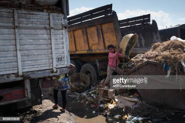 A girl empties a basket of garbage into a full dumpster as Council workers begin to clear garbage during the cleanup of the market of Anosibe in the...