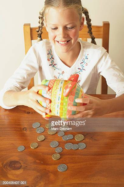 Girl (10-12) emptying piggy bank onto table, smiling, elevated view