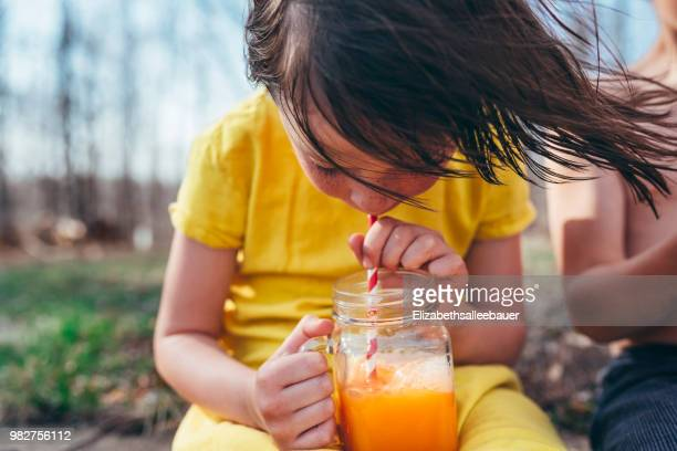 girl enjoying a summer drink - orange juice stock pictures, royalty-free photos & images