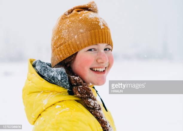 屋外雪の冬の日を楽しむ女の子 - ピンクの頬 ストックフォトと画像
