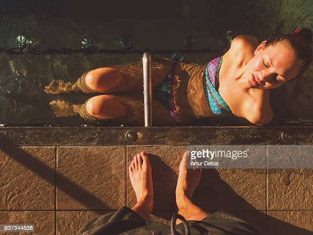 Girl enjoying and relaxing in a spa swimming pool with natural warm waters during Christmas travel vacations in the Pyrenees.