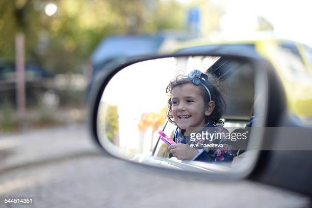 Girl (4-5) enjoying car trip and looking in rearview mirror