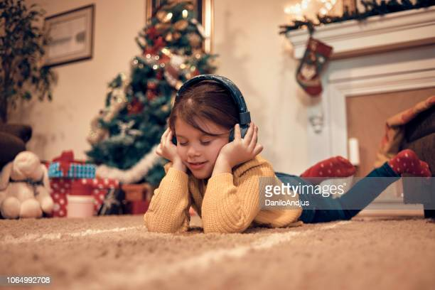 girl enjoying christmas ambient - christmas music stock pictures, royalty-free photos & images