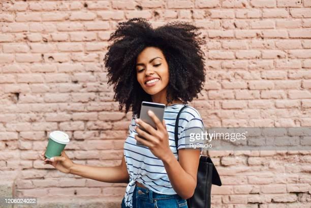 fille appréciant le café et podcasting à l'extérieur - social media photos et images de collection
