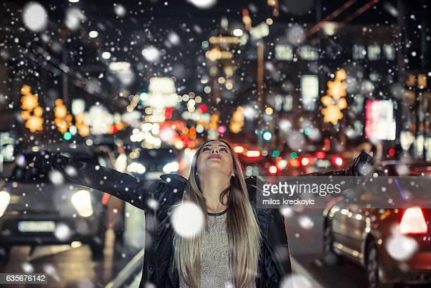 Girl enjoying firs snow in city