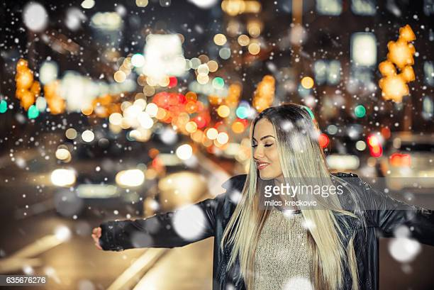 Girl enjoying firs snow in city