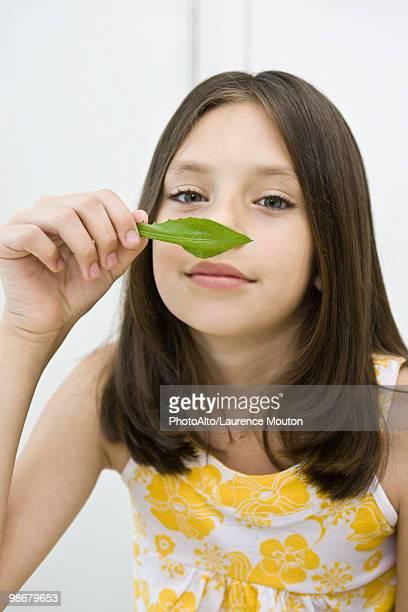 Girl enjoying fragrance of fresh herb