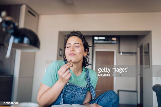 girl enjoying her favorite cookie at home - satisfaction stock pictures, royalty-free photos & images