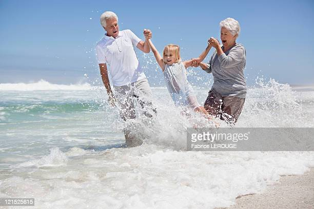 Girl enjoying on the beach with her grandparents