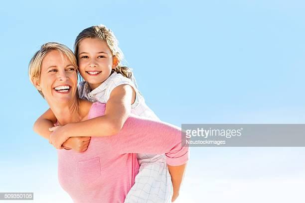 Girl Enjoying Piggyback Ride From Mother Against Clear Blue Sky