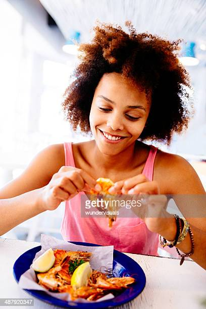 girl enjoying seafood in restaurant - shrimp stock photos and pictures