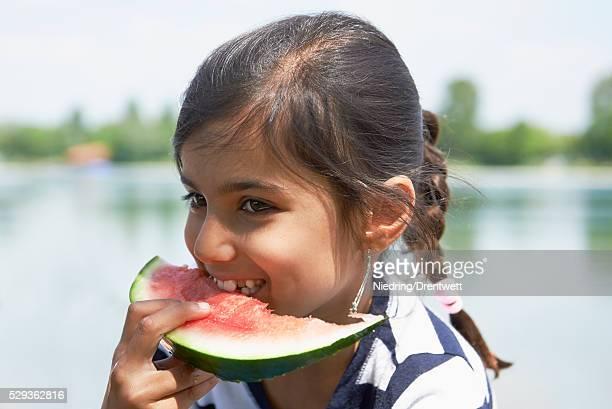 Girl enjoying slice of watermelon at picnic, Munich, Bavaria, Germany