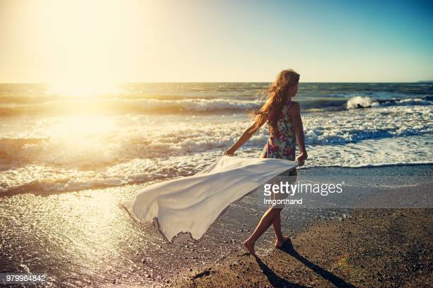 Girl enjoying sunset on a windy beach