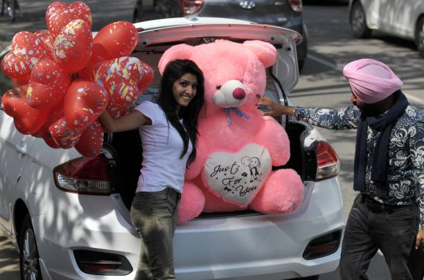 A girl enjoying the Valentine's Day with red balloons and a big teddy at sector 10 on February 14 2017 in Chandigarh India