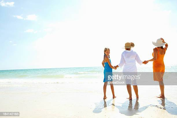 Girl enjoys a walk with mother and grandmother on beach