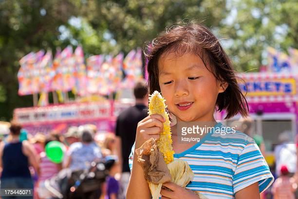 Girl enjoys corn on the cob at carnival