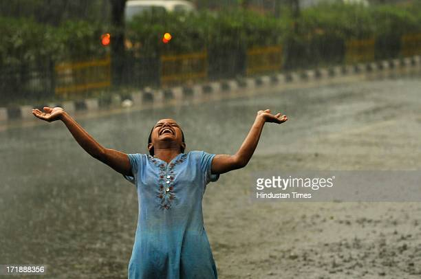 A girl enjoys during a heavy rainfall after a hot and humid afternoon on June 29 2013 in Noida India Weather department forecast the country will...