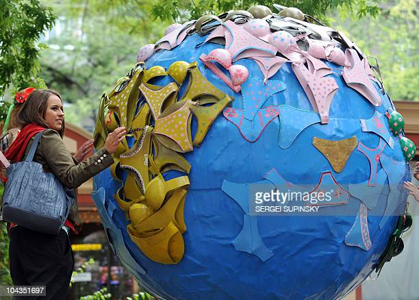 A girl examines a decorative sculpture depicting a terrestrial globe decorated with womens' brassieres and panties instead of continents in Kiev on...