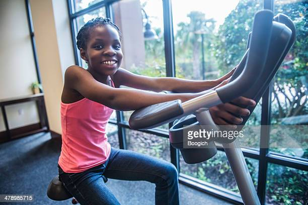 girl excercing on stationary bike - daily sport girls stock pictures, royalty-free photos & images