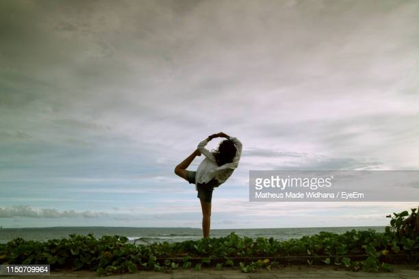girl exercising while standing by sea against sky - made widhana stock photos and pictures