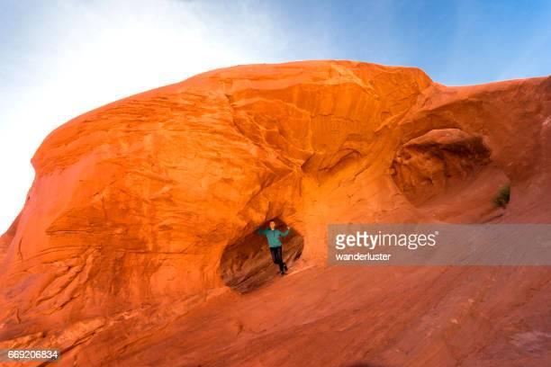 girl explores anasazi dwelling in mystery valley, az - monument valley tribal park stock photos and pictures