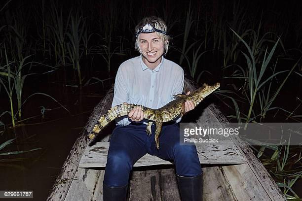 girl exploring jungle river night holding cayman