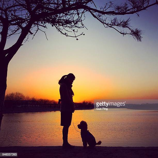 Girl face to face with her dog standing beside lake enjoy the sunset moment