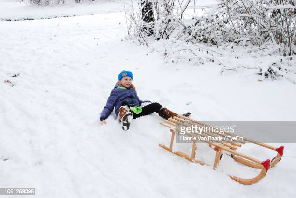 Girl Falling From Sled On Snow During Winter