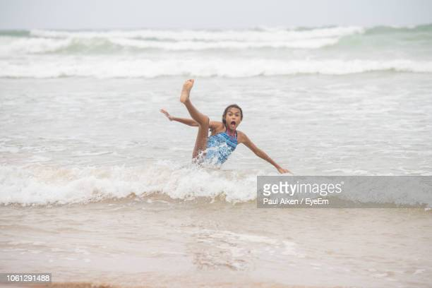 girl falling while playing in sea - aikāne stock pictures, royalty-free photos & images