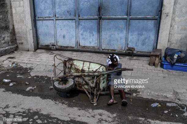A girl falls as he drags a hand cart at a local market in PortauPrince on January 23 2020