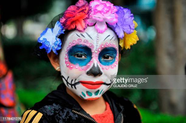 A girl fancy dressed as Catrina takes part in the Catrinas Parade along Reforma Avenue in Mexico City on October 26 2019 Mexicans get ready to...