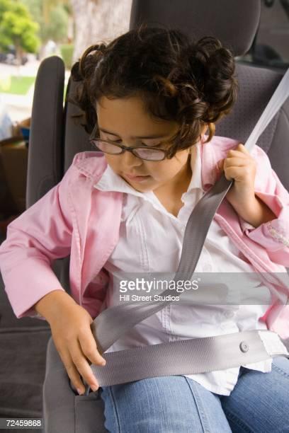 Girl fastening seatbelt in backseat of car