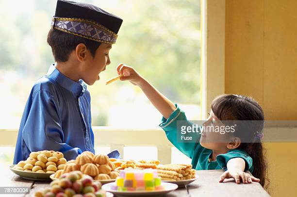 Girl Feeding Boy Sweets for Malaysian New Year