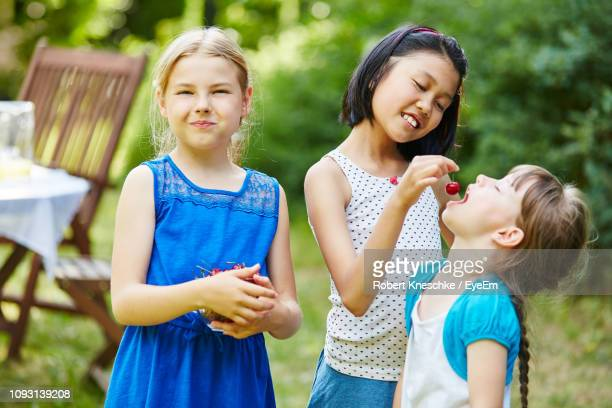 Girl Feeding Cherry To Friend During Party At Yard