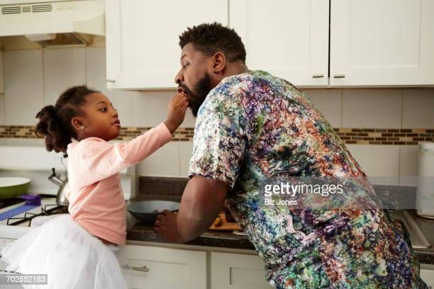 girl feeding father in kitchen - genderblend stock pictures, royalty-free photos & images