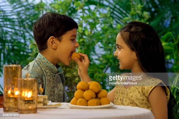 Girl feeding her brother a laddoo