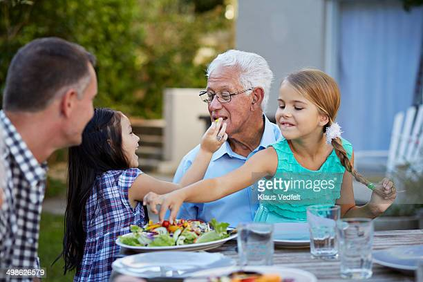 Girl feeding her grandfather at outside dinner