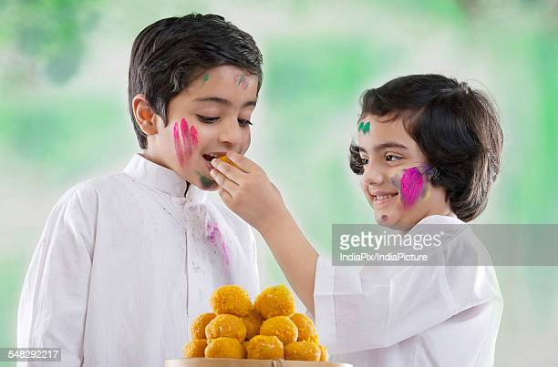 girl feeding laddoo to a boy - mithai stock pictures, royalty-free photos & images