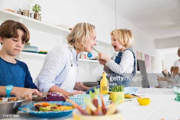 girl feeding mother asparagus at kitchen table - hell beleuchtet stock-fotos und bilder