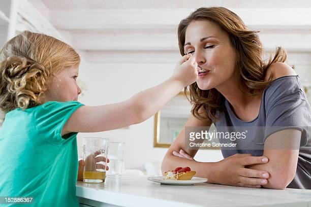 girl feeding mother breakfast - genuss stock-fotos und bilder