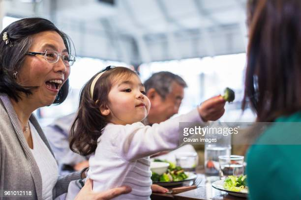 Girl feeding mother while sitting with grandparents at table in restaurant