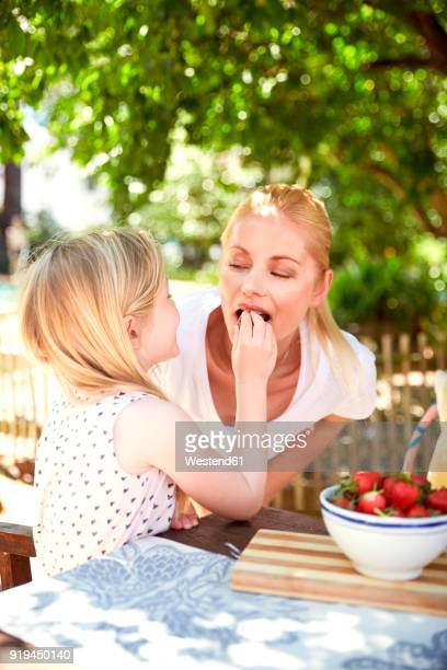 Girl feeding mother with stawberries