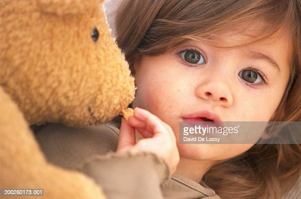 Girl (18-24 months) feeding stuffed toy, close-up
