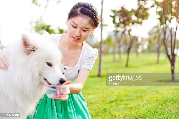 Girl feeding the dog drinking water on grass