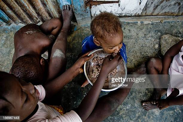 A girl feeds his younger brother by rice in the slum of Cité Soleil PortauPrince Haiti 22 July 2008 Rice is a basic source of nutrition for all...