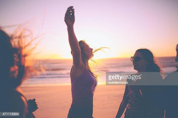 Chica siente libre en contra de un atardecer en la playa con amigos